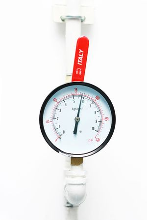 An pressure meter build on white wall.