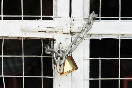 A gate locked with a golden yale and chain Stock Photo - 3085663