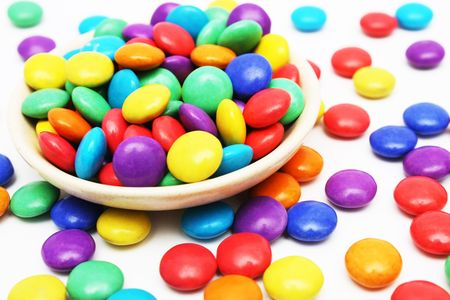 childhood obesity: A lot of colorful candies on small dish and some scattered around it.
