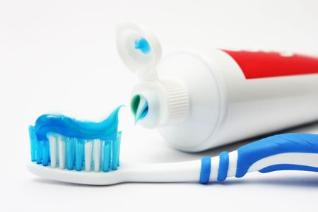 Blue dental brush with tooth paste on white background.