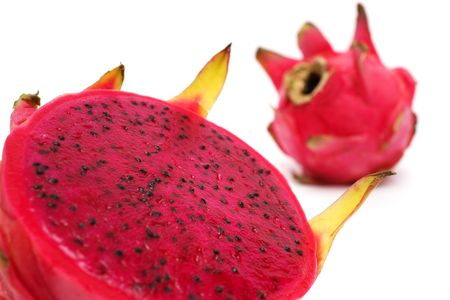 Close up of an half red dragon fruit over white background.