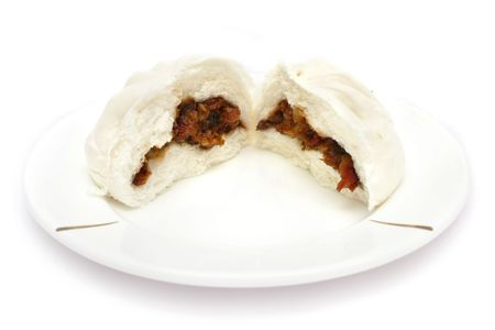 barbecued: A Chinese barbecued pork bun tear into two half. Stock Photo