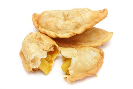 Three Malay curry puffs with potato pieces inside on white background. photo