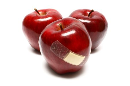 Injured apples with plaster on white background.