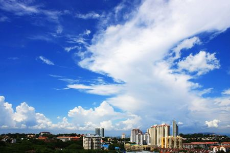 Cityscape over cloudy blue skies on sunny day.