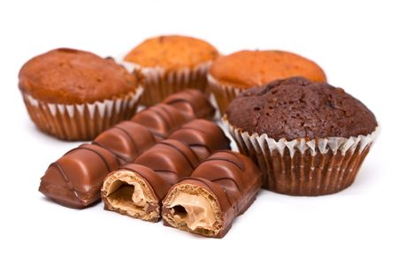 Milk chocolate bars and muffin on white background. photo
