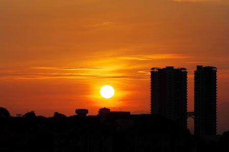 Golden sunrise cityscape with twin tower condominium. Standard-Bild