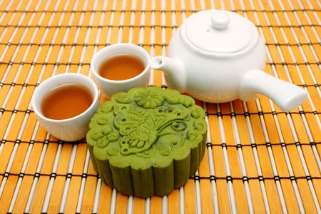 A greentea mooncake put together with teacup and teapot.