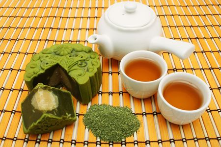 Greentea mooncake slice into quarter put together with teacup and teapot.
