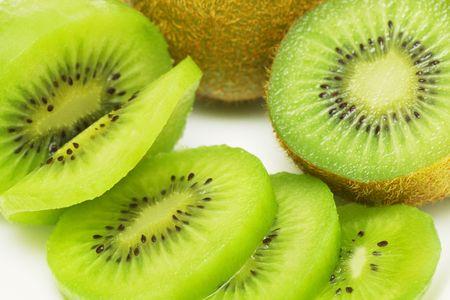 Kiwi fruit sliced into pieces on white background.