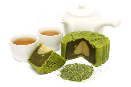 Greentea mooncake sliced into quarter put together with teacup and teapot. Stock Photo