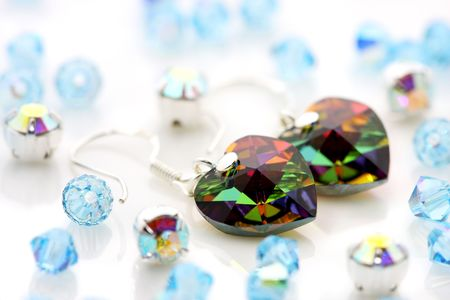 A pair of love shape swarovski earrings puts together with beads. photo