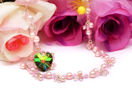 A heart shape bead and pink necklace put with flowers. Standard-Bild