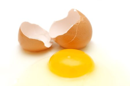 albumin: Broken egg with yolk, albumin and eggshell over white background.