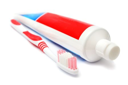 Tooth brush beside toothpaste on white background.