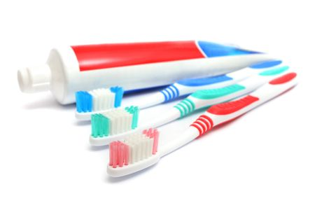 Tooth brush beside toothpaste on white background. photo