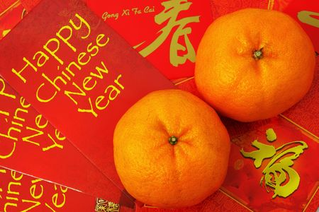 Two mandarin orange put on red packets.