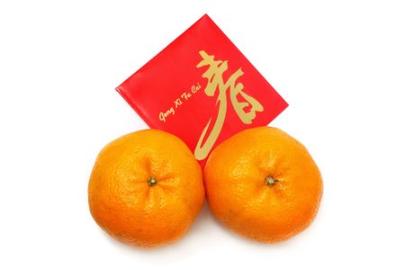 Two mandarin oranges and red packet isolated over white background.