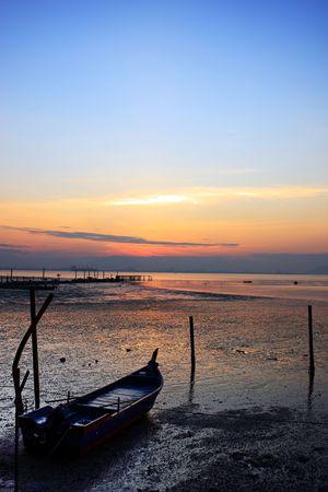 docking: Sunrise view with fishing boat docking at coastal.