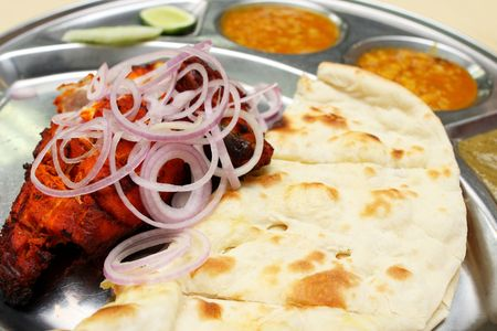 Close up of tandoori chicken and naan bread on steel plate.