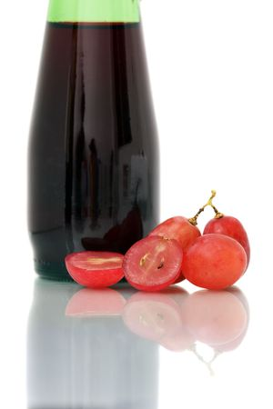 Bunch of red grapes on white plate beside wine bottle. photo