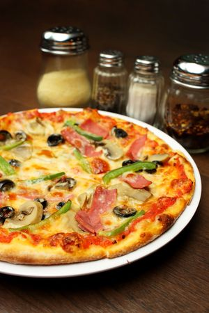Close up of a pizza with seasoning on brown table.