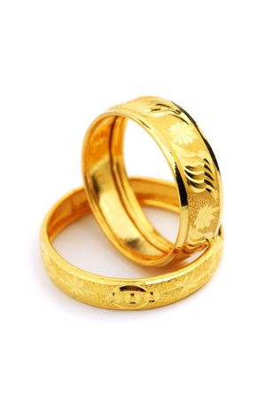 Two golden rings standing on white background. Stock Photo