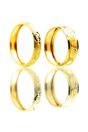 Two golden rings standing on white background. photo