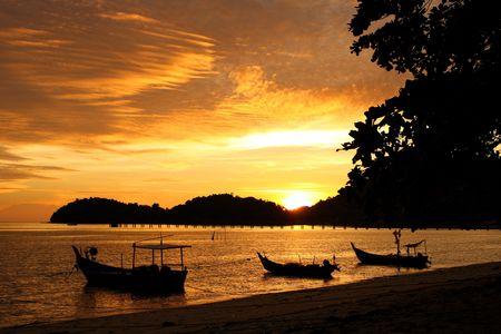 docking: Sunset view with fishing boat docking at coastal.