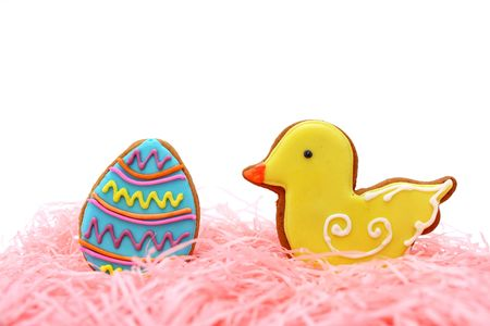 Close up of easter egg and duck cookies on pink ribbons over white background. Stock Photo - 7262292