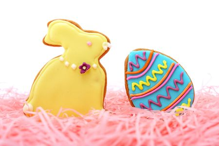 Close up of easter egg and bunny cookies on pink ribbons over white background. Stock Photo - 7262294