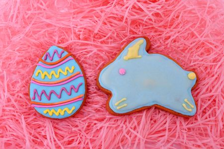 Close up of easter egg and bunny cookies on pink ribbons as background. photo