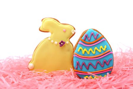 Close up of easter egg and bunny cookies on pink ribbons over white background. photo