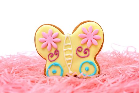 Close up of butterfly cookie on pink ribbons over white background. photo