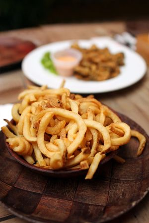 Close up of French fries with other dishes on wooden table. photo