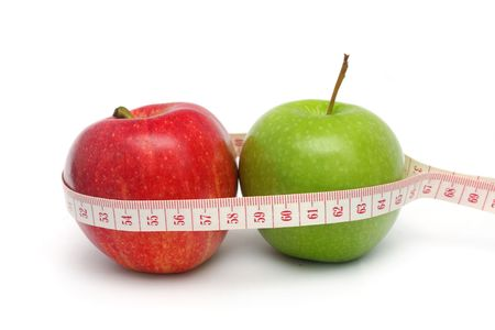 Close up of red and green apple with measuring tape isolated on white background. photo