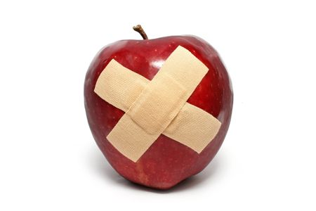 An injured red apple with plaster on it isolated over white background.
