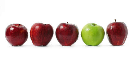 A green apple being stood out among red apples isolated on white background. Stock Photo