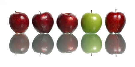 A green apple being standout among red apples isolated on white background. Stock Photo