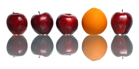 An orange being standout among red apples isolated on white background.