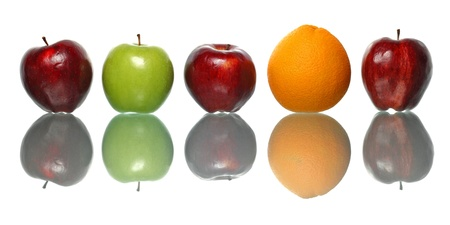 symetry: An orange and green apple standout among red apples isolated on white background. Stock Photo