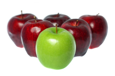 A green apple put in the middle of red apples isolated on white background.