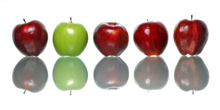 standout: A green apple being standout among red apples isolated on white background. Stock Photo