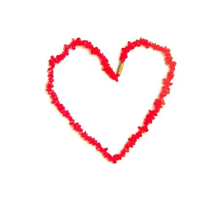 coral beads in the shape of a heart on a white background