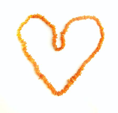 amber beads in the shape of a heart on a white background