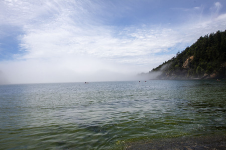 The emerald sea in Bowman's Bay yields to the mist.  The kayakers sail in to the fog with the hope of blue skies peeking out behind the clouds.