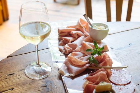Calix with sparkling Prosecco Superiore di Valdobbiadene-Conegliano and starter dish on cutting board with salami, Trieste's ham, Parma's raw ham and mortadella. Horseradish as sauce