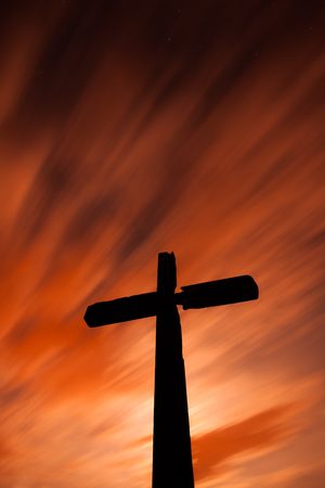 A crucifix with fast red clouds at night.