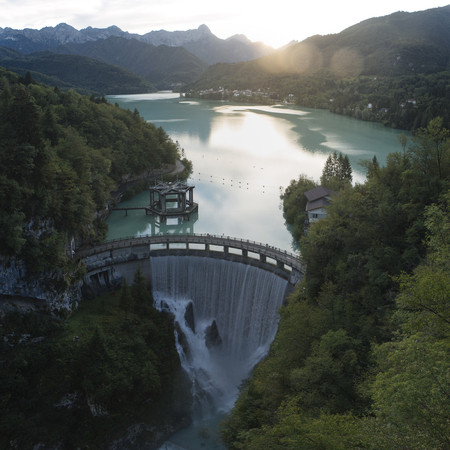 Dam on the Barcis lake at sunset, with the village in the background. It was created in 1954 for the exploitation of hydroelectric power. Stock Photo