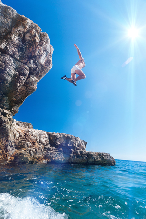 A young man jumps from a cliff, Krk Island, Croatia.